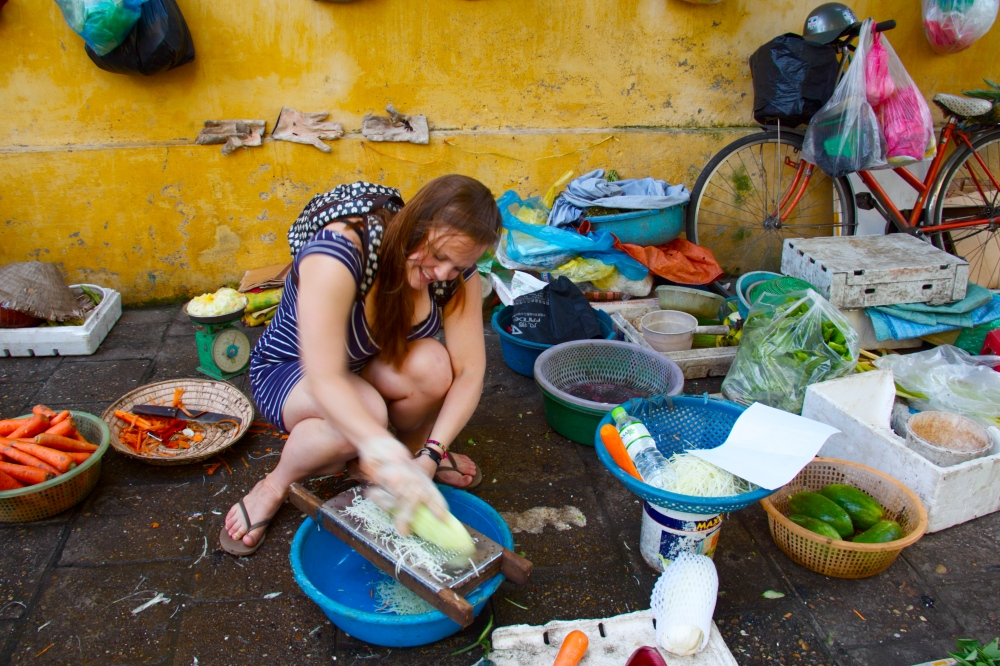 Putting some elbow grease in by grating papaya at the market.